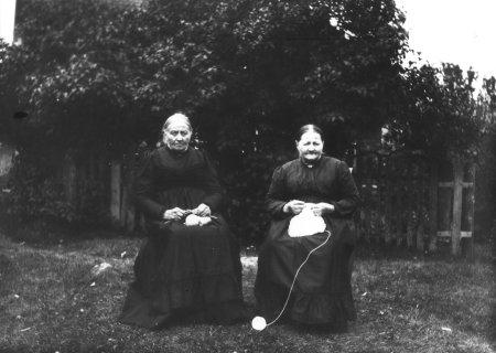 Gammelt fotografi av to eldre damer som sitter og strikker